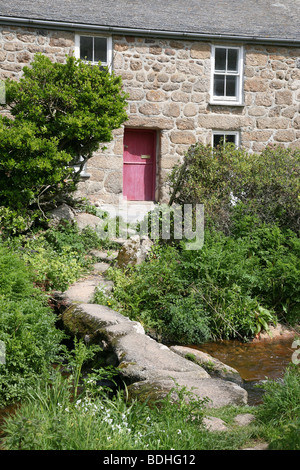 Old stone built country cottage with a clapper bridge crossing the stream in front of it Cornwall, England - Stock Photo