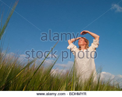Woman standing in tall grass with arms raised and eyes closed - Stock Photo