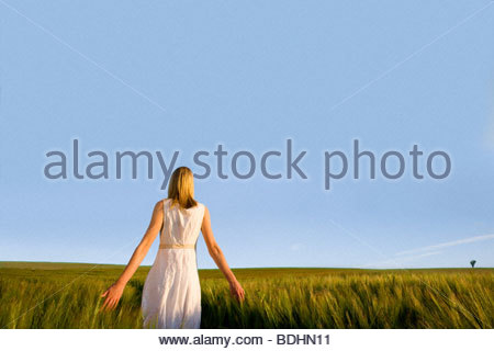 Teenage girl walking through barley field - Stock Photo