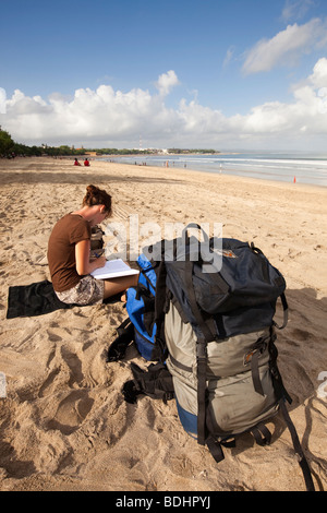 Indonesia, Bali , Kuta, high season backpacker on the beach in early morning waiting to find vacant hotel room - Stock Photo