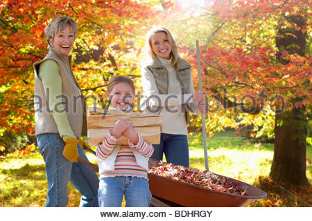Three generation family doing yard work in autumn - Stock Photo