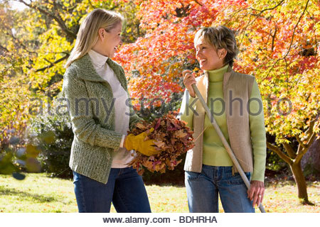 Mother and daughter doing yard work in autumn - Stock Photo