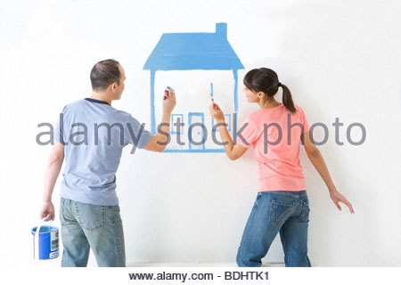 Couple painting house on wall with paintbrushes - Stock Photo