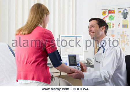 Doctor checking female patient's blood pressure in doctor's office - Stock Photo