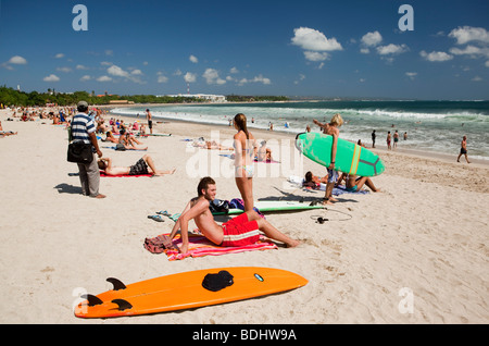 Indonesia, Bali, Kuta, beach, surfers resting on sand at waters edge - Stock Photo