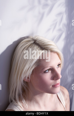 young woman sat in the light from a window, looking off camera - Stock Photo