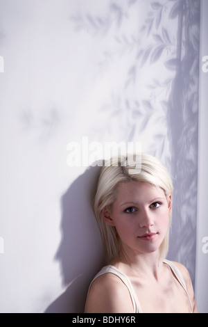 young woman sat in the light from a window, looking to camera - Stock Photo