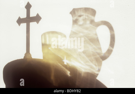 Shadow on white wall of circular table with free-standing crucifix and glass jug with glass containing liquid - Stock Photo