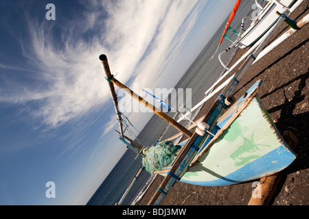 Indonesia, Bali, Amed, colourfully painted outrigger fishing boats on the black volcanic sand beach - Stock Photo