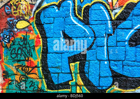 Rough wall surface covered with colorful graffiti. Urban street art background. - Stock Photo