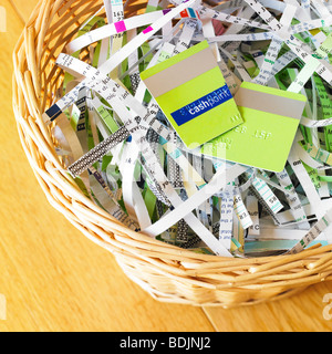 Shredded documents and cut credit card in waste bin - identity theft protection. - Stock Photo
