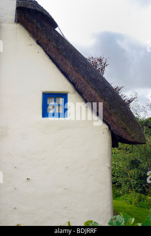 The end of an old thatched cottage with a small blue window - Stock Photo
