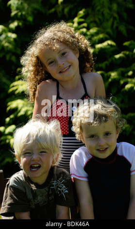 Three happy children sitting on a garden seat posing for a photo - Stock Photo