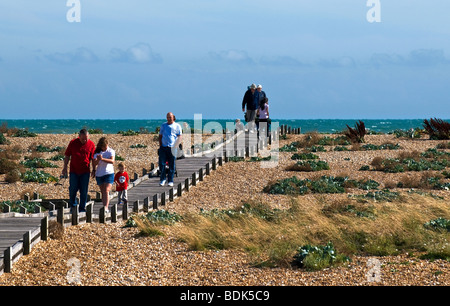 People walking along the boardwalk across the shingle beach at Dungeness in Kent. - Stock Photo