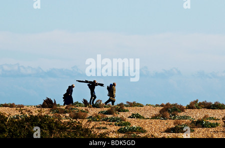 Silhouette of three anglers walking along the shingle beach at Dungeness in Kent. - Stock Photo