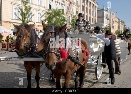 Horse drawn carriages wait for customers in the main square of the Polish town of Krakow - Stock Photo