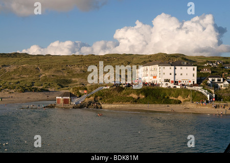 Holiday makers on beach in front of Ponsmere Hotel and Sunset Bar in Perranporth, Cornwall - Stock Photo