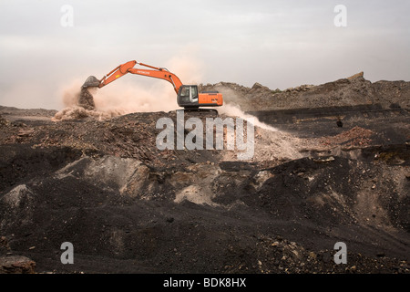 Diggers loading trucks with dusty ore and rock to expose coal in the Wuda coal field near Wu Hai, Inner Mongolia - Stock Photo