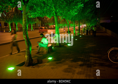 ORDOS, INNER MONGOLIA, CHINA - AUGUST 2007: Up-lighters cast a green glow on a main street at night. - Stock Photo