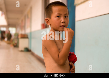 PU LIAN TA COAL MINE, ORDOS, INNER MONGOLIA, CHINA - AUGUST 2007: The son of a miner plays beside the miners' accommodation - Stock Photo