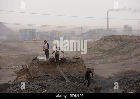 WUDA COAL FIELD, WU HAI, INNER MONGOLIA, CHINA - AUGUST 2007: Liang Yan Fa carries baskets of sifted coal to make - Stock Photo