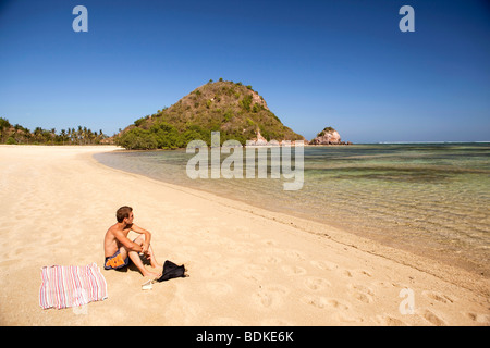 Indonesia, Lombok, Kuta, one solitary male sunbather on the beach - Stock Photo