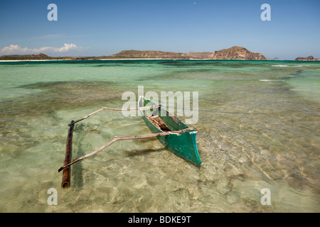 Indonesia, Lombok, Tanjung, beach, fishermens dugout boat in shallow water - Stock Photo