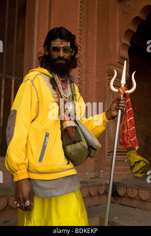 A Sadhu holds a trident in the Indian city of Varanasi (Benares). The Sadhu is a Shiva devotee and a pujari (priest) - Stock Photo