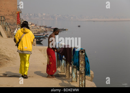 A Sadhu walks along the riverside in the city of Varanasi (Benares). The Sadhu holds a trident, the other man wears - Stock Photo