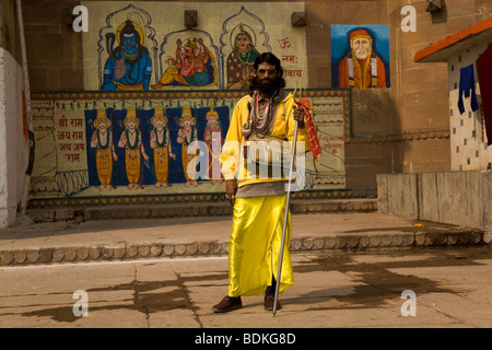 A Sadhu in the Indian city of Varanasi (Benares). He stands in front of a painted temple. - Stock Photo