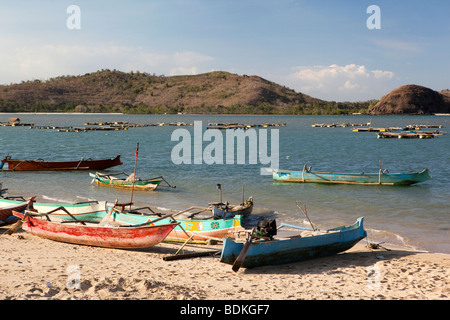 Indonesia, Lombok, Awang, traditional colourfully painted outrigger fishing boats on the beach - Stock Photo