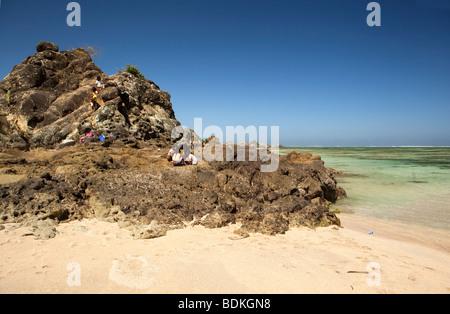 Indonesia, Lombok, Kuta, beach, local children playing on rocky headland - Stock Photo