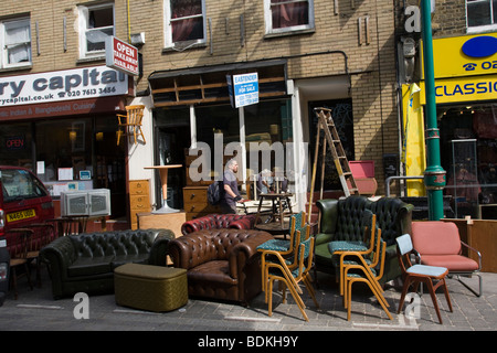 Furniture for sale stacked in roadway, 'Brick Lane' ' Tower Hamlets' London GB UK - Stock Photo