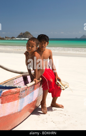 Indonesia, Lombok, South Coast, Selong Blanak, beach two young boys sat on colourfully painted fishing boat - Stock Photo