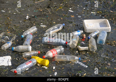 Plastic bottles, polystyrene crates and other detritus floating on water. - Stock Photo