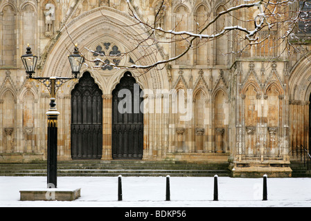 Main doors in the west face of York Minster, North Yorkshire, England on a snowy winter's day. - Stock Photo