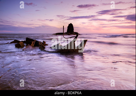 The pink of pre-dawn light illuminates the wreck at Black Nab, Saltwick an hour before sunrise - Stock Photo