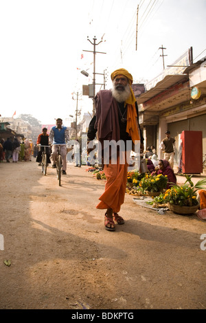A Sadhu walks along a busy street in the Indian city of Varanasi (Benares). The Sadhu walks past people selling - Stock Photo