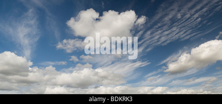 Altocumulus undulatus and cumulus clouds - Stock Photo