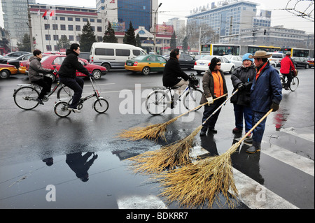 A team or groups of street cleaners in Beijing use besom brooms to clean water off the street for motorists and - Stock Photo