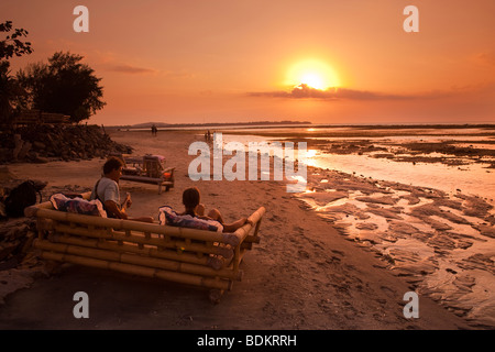 Indonesia, Lombok, Gili Air, north coast, sunset point, people enjoying setting sun playing guitar - Stock Photo