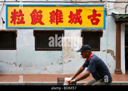 An old man cycling pass the famous Jonker Street in Malacca, a Unesco World Heritage site in Malaysia - Stock Photo