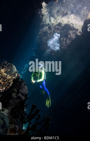 a pretty female scuba diver in a cave with sunbeams - Stock Photo