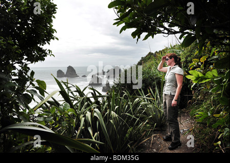 A tourist looks out to a stormy sea pounding the West Coast of South Island of New Zealand - Stock Photo