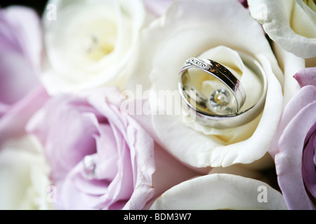 Wedding rings bands closeup in bridal flowers bouquet - Stock Photo