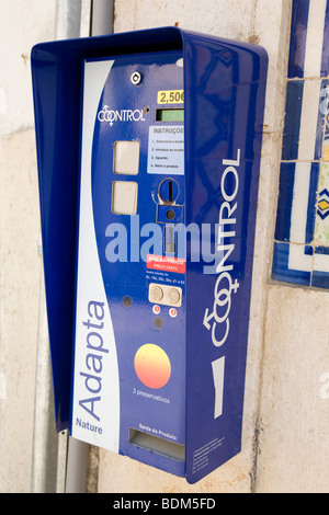 A condom vending machine hangs on a wall in a street in Portugal. - Stock Photo