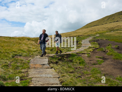Two walkers on new flagged section of the Pennine Way path, Kinder Scout, near Edale, Peak National Park, Derbyshire, - Stock Photo