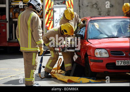 Firefighters demonstrate how to cut free a driver from a crashed car at the Preston Circus Fire Station Open Day - Stock Photo
