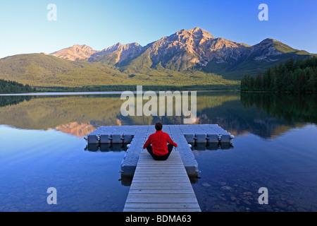 Middle age male meditating on dock at Pyramid Lake, Jasper National Park, Alberta, Canada. - Stock Photo