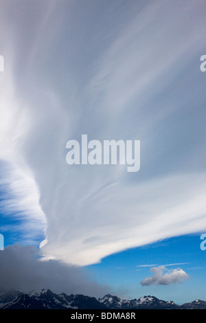 Tall lenticular clouds over mountain tops where dark stormy clouds drop snow in the Antarctic summer of South Georgia - Stock Photo